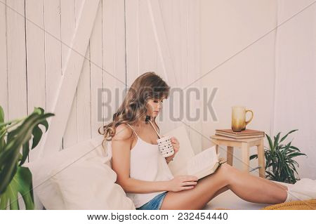 Young Woman At Home Sitting On Bed And Relaxing In Bedroom Reading Book And Drinking Coffee Or Tea