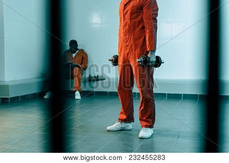 Cropped Image Of Prisoner Training With Dumbbells In Prison Room
