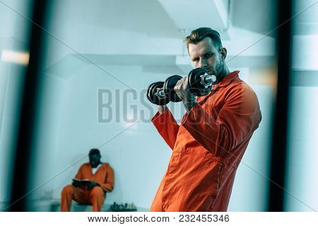 Prisoner Training With Dumbbells In Prison Room