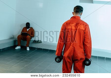 Rear View Of Prisoner Training With Dumbbells In Prison Cell