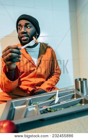 African American Criminal Eating In Prison Cell