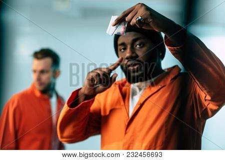 African American Prisoner Pointing On Drugs At Prison Cell