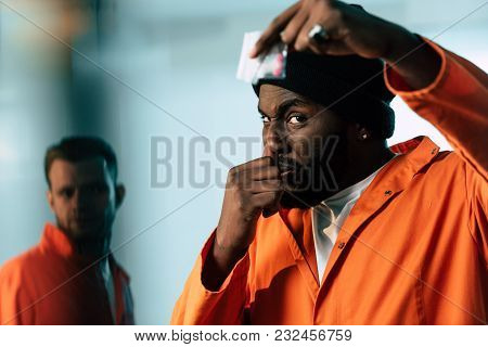 African American Prisoner Holding Drugs At Prison Cell