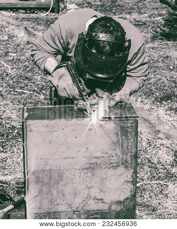 a welder puts the seam on the metal electro arc welding, black and white photo