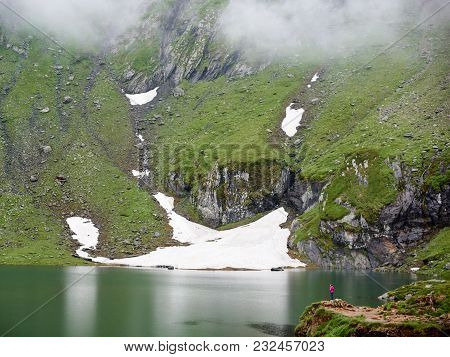 Mighty Mountains Are Covered With Fog And The Lake At The Foot, Transylvania, Romania. In The Distan