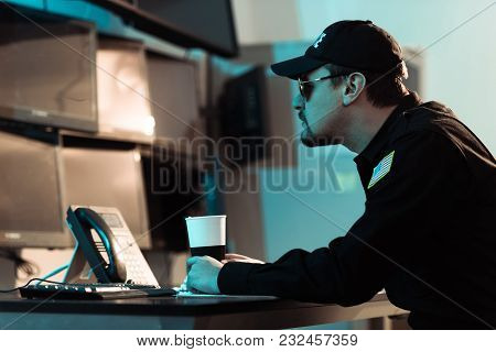 Side View Of Prison Guard Sitting With Cup Of Coffee And Monitoring People In Jail