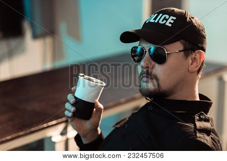 View Of Prison Guard Holding Cup Of Coffee