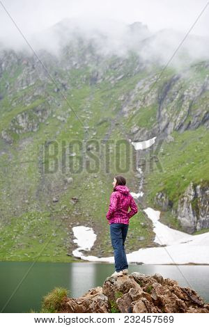 Pretty Young Girl Hiker With Hands In Pockets Standing On The Edge Of Rocky Cliff Looking At The Blu