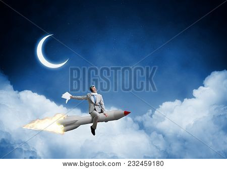 Conceptual Image Of Successful Businessman In Suit Flying On Jet Rocket With Blue Night Skyscape Wit