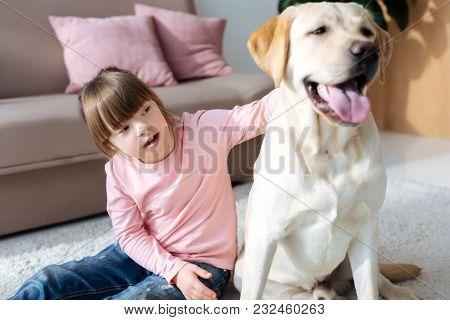 Child With Down Syndrome Stroking Labrador Retriever