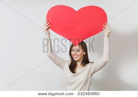 Attractive Young Smiling Woman Holding Big Red Heart In Hands Isolated On White Background. Copy Spa