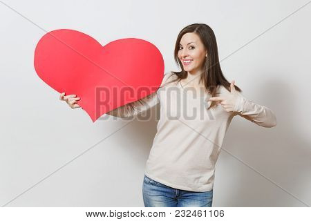Attractive Young Smiling Woman Pointing Big Red Heart In Hands Isolated On White Background. Copy Sp