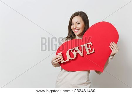 Effective Young Smiling Woman Holding Big Red Heart, Wooden Word Love On White Background. Copy Spac