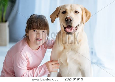 Happy Child Girl With Down Syndrome Cherishing Labrador Retriever