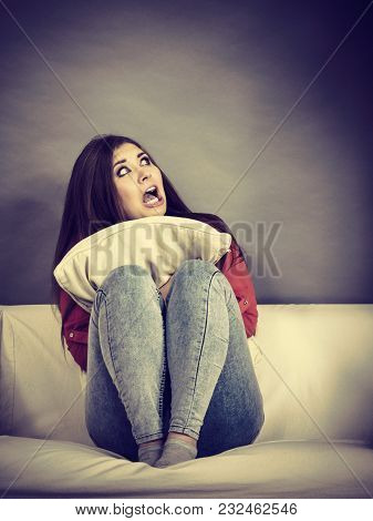 Scared Bullied Teenage Woman Sitting On Sofa Holding Pillow And Screaming Being Terrified.