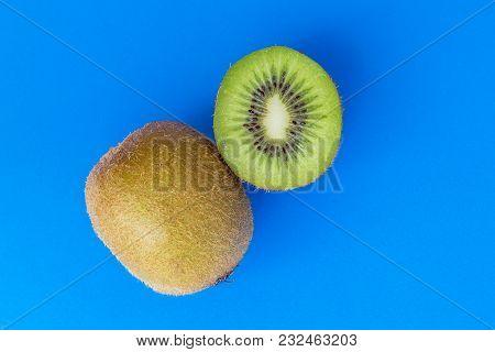 Ripe Whole Kiwi Fruit And Half Kiwi Fruit Isolated On Blue Background