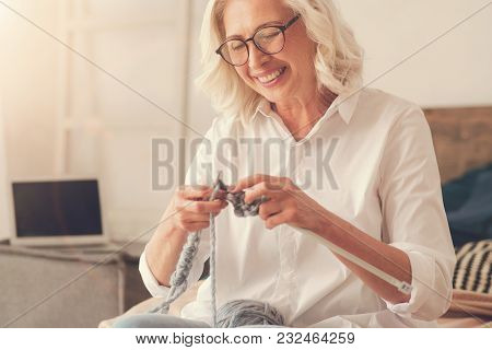 For My Children. Happy Delighted Aged Woman Holding Knitting Needles And Smiling While Making A Scar