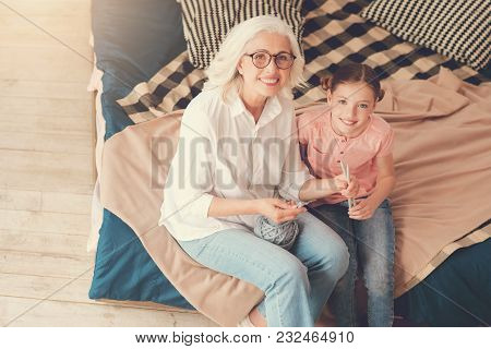 My Hobby. Joyful Positive Nice Girl Smiling And Looking At You While Holding Knitting Needles