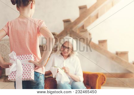 For My Grandma. Nice Pretty Pleasant Girl Looking At Her Grandmother And Hiding A Present While Inte