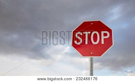Low Angle Shot Of A Stop Sign With Sky Clouds Background