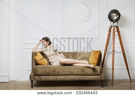 Fashionable, Sexy And Beautiful Brunette Model Girl, In Beige Dress, Posing On The Sofa At Luxury Ba
