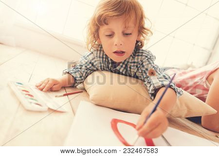 Creative Hobby. Positive Delighted Cute Child Lying On The Floor And Holding A Brush While Painting