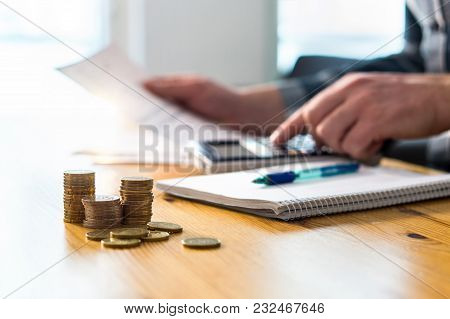 Man Using Calculator And Reading Financial Document Paper. Entrepreneur, Bookkeeper Or Accountant Wo