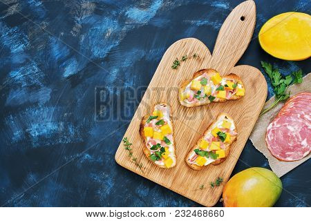 Mango, Ham And Cream Cheese On Crispy Toast Are Served On A Cutting Board. Top View, Space For Text.