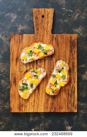 Toast With Ham And Mango On Wooden Board, Dark Background, Top View.