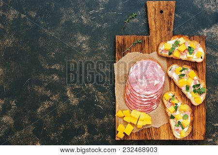 Three Toasts With Ham, Cream Cheese And Mango On A Cutting Board, Rustic Dark Background. Top View,