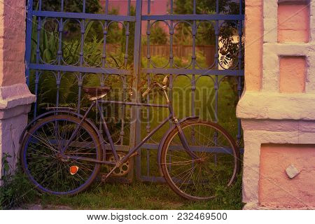 The Old Bike Parked At The Fence