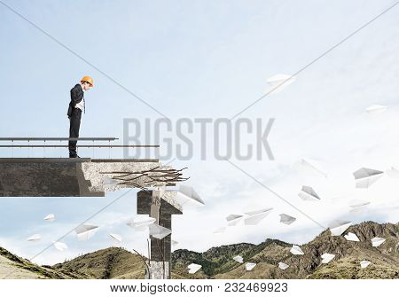 Young Engineer In Suit And Helmet Looking Down While Standing Among Flying Paper Planes On Broken Br