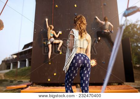 Back View Of Active Young Woman In Leggings Standing With Rope On Shoulder Against Artificial Traini
