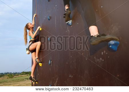 Bottom View Of Two Young Climbers Approaching To Finishing Point On The Speed Track Of Climbing Comp