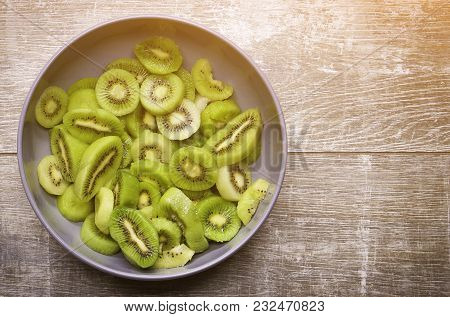 Kiwi In A Plate On A Wooden Background.