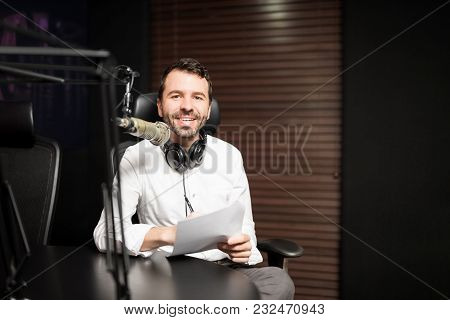 Portrait Of Happy Young Man Working As Radio Host At Radio Station