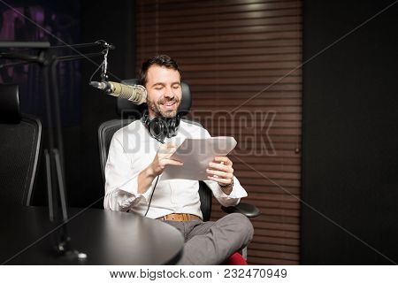 Happy Young Male Radio Host Sitting At A Table With Headphones Reading A Script Paper And Broadcasti