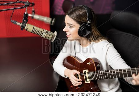 Smiling Woman Singer With Headphones Singing A Song And Playing Guitar Into Mic At Radio Station