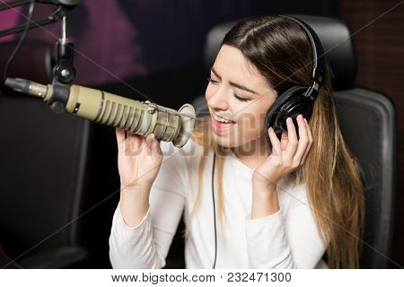 Good Looking Young Female Singer Wearing Headphones Singing Song Live On Microphone At Radio Station
