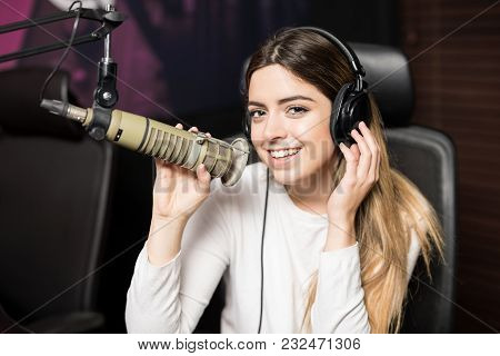 Beautiful Woman With Headphones Singing A Song On To A Microphone At Radio Station, Live Music Broad