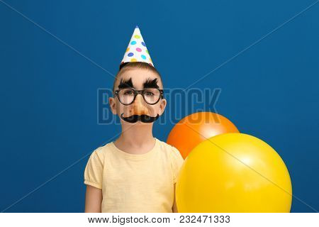 Cute little boy in funny disguise on color background. April fool's day celebration