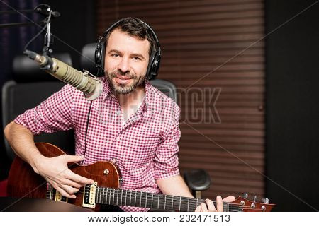 Handsome Young Male Singer Playing Guitar And Singing In Microphone At Radio Station