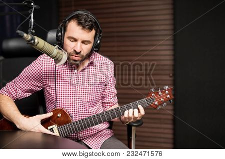 Young Male Music Artist Singing In Microphone And Play Guitar At Radio Station