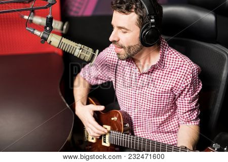 Handsome Young Male Singer With Headphones Singing A Song And Playing Guitar Into Mic During A Radio