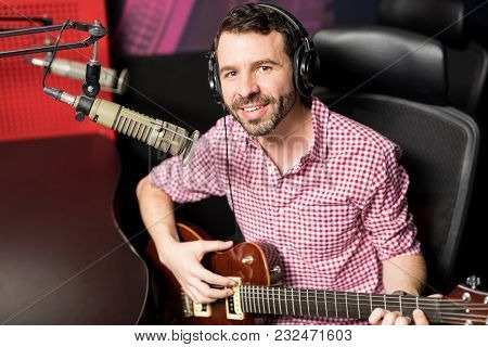 Hispanic Young Male Singer Making An Eye Contact While Playing Guitar And Singing In Microphone At R