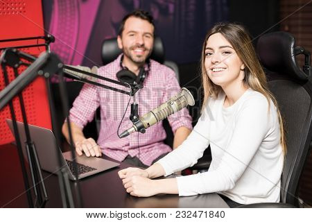 Happy Young Female Radio Host With Male Coworker Hosting A Talk Show In Radio