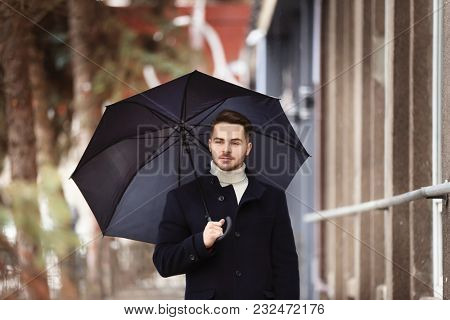 Young man in warm clothes with dark umbrella outdoors