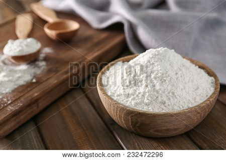 Wheat flour in bowl on wooden table