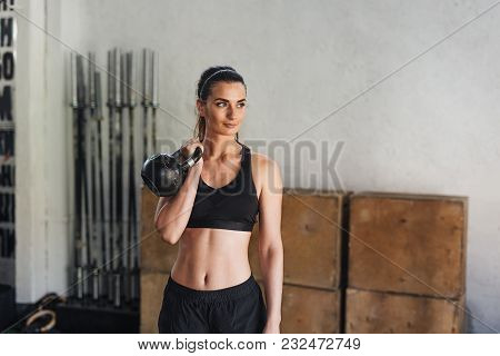 Young Athlete In Sportswear Doing Workout With Kettlebell In Sport Club