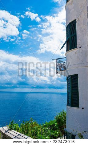 Beautiful view of the lighthouse on the sea. Beautiful coast of the Adriatic Sea. Blue sea white clouds.